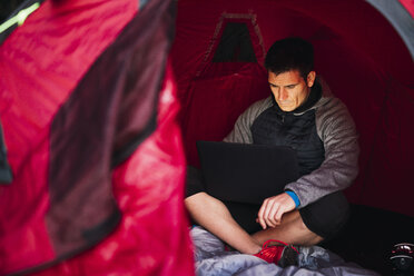 Man camping in Estonia, sitting in tent, using laptop - KKA02792