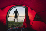 Man camping in Estonia, standing in front of tent, watching sunset - KKA02795