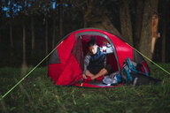 Man camping in Estonia, sitting in his tent, holding latern - KKA02798