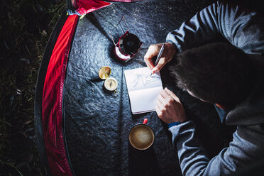 Man camping in Estonia, drawing in his sketchbook at night - KKA02804