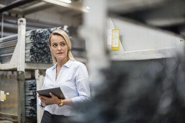 Blond woman holding tablet in high rack warehouse - DIGF05417