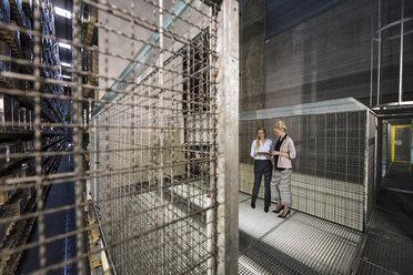 Women using laptop in high rack warehouse - DIGF05420