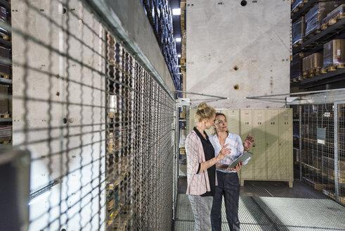 Women using laptop in high rack warehouse - DIGF05423