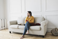 Relaxed young woman with smartphone sitting on the couch at new home looking at distance - KMKF00595