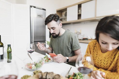 Man checking messages on mobile phone while having lunch with his girlfriend at home - KMKF00598