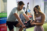 Instructor helping man on spinning bike in a gym - JSMF00478