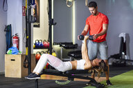 Personal trainer assisting client with weight training, lifting dumbells, lying on bench - JSMF00493