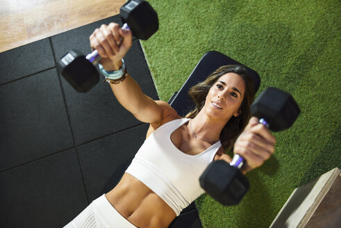 Woman training with dumbbells in a gym - JSMF00499