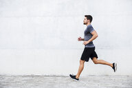 Athlete running in front of white wall - JSMF00514