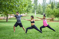 Young people exercising yoga in a park - JSMF00529