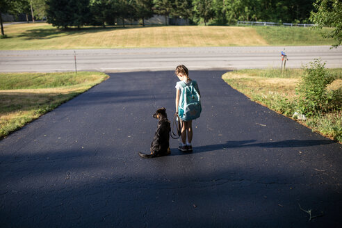 Rear view of girl carrying backpack while standing with dog on road - CAVF50596