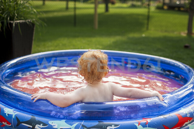 Rear view of shirtless baby boy sitting in wading pool at yard - CAVF50638