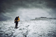 Rear view of male hiker walking on snow covered mountain against cloudy sky - CAVF50647