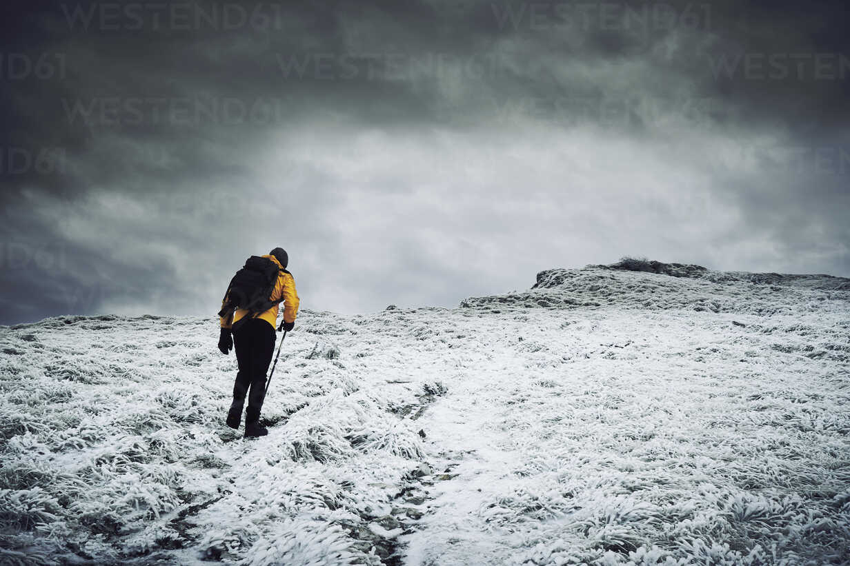 Rear view of male hiker walking on snow covered mountain against cloudy sky - CAVF50647 - Cavan Images/Westend61