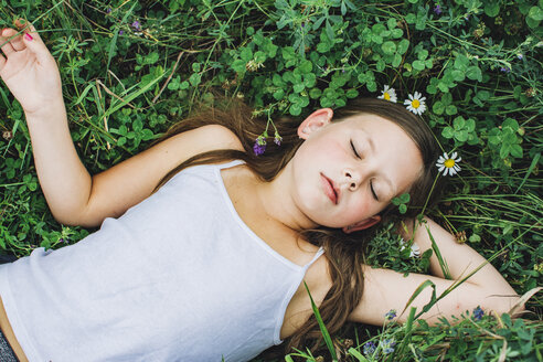 High angle view of girl sleeping on field amidst plants at park - CAVF50653