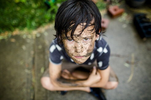 High angle portrait boy with dirty face sitting on footpath at yard during rainy season - CAVF50659