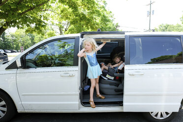 Cute girl hanging at entrance while sister sitting in car - CAVF50665