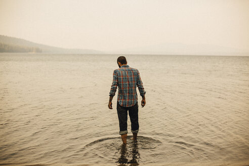Rear view of man standing in lake against clear sky - CAVF50707