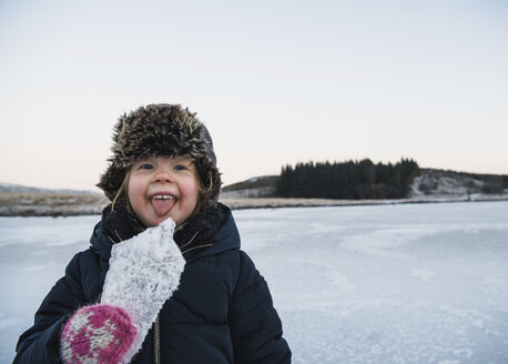 Portrait of playful girl sticking out tongue while holding ice - CAVF50749