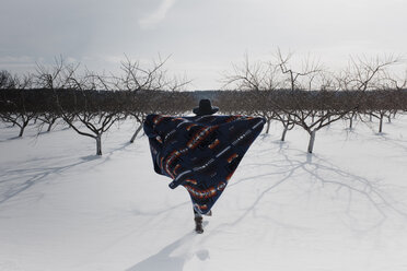 Rear view of woman with blanket walking on snow covered field - CAVF50755