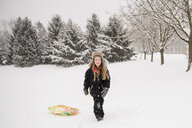 Full length of girl wearing warm clothing while walking with sled on snowy field against trees during snowfall - CAVF50761