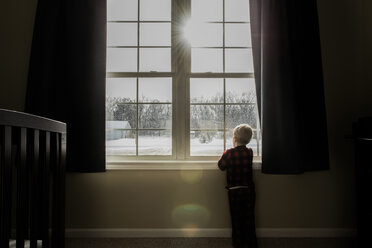 Rear view of boy looking through window while standing at home during winter - CAVF50764