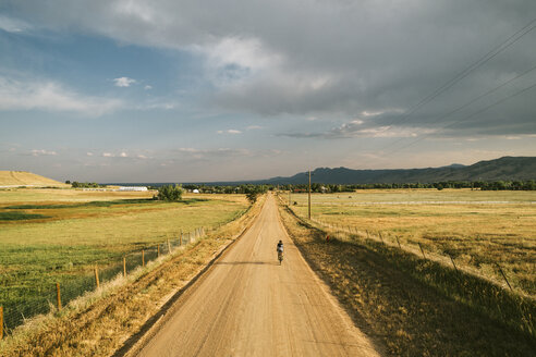 Rear view of man riding bicycle on dirt road against cloudy sky - CAVF50773