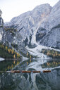 Boats moored at calm lake by mountain against sky during winter - CAVF50788