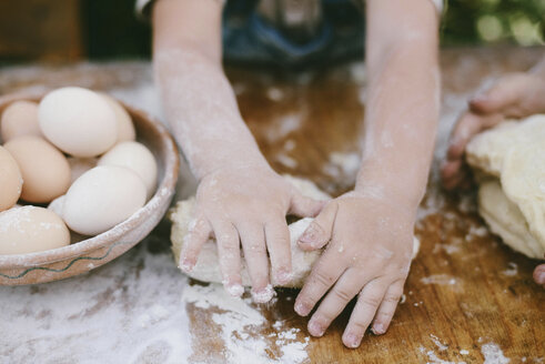 Cropped hands of mother and son kneading dough on wooden table at yard - CAVF50818