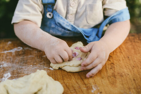 Midsection of boy kneading dough on wooden table at yard - CAVF50824