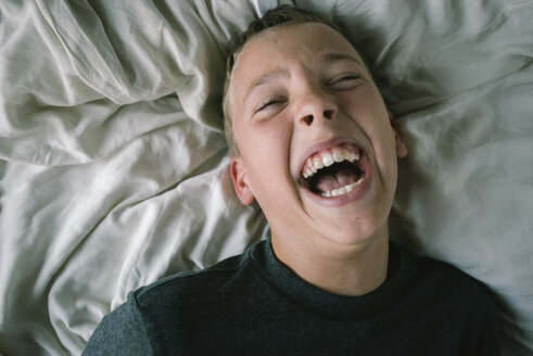 High angle view of boy laughing while lying on bed at home - CAVF50854