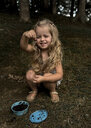 Playful girl holding insect while crouching at forest - CAVF50860