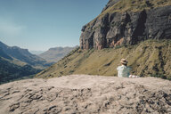 Rear view of woman sitting on mountain during sunny day - CAVF50884