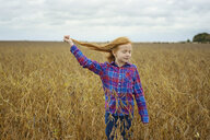 Carefree girl with eyes closed holding her hair while standing amidst soybean's field against sky - CAVF50902
