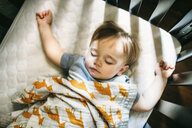 Overhead view of cute baby boy sleeping in crib at home - CAVF50905