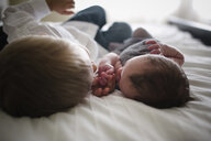 Boy lying by newborn brother on bed at home - CAVF50983