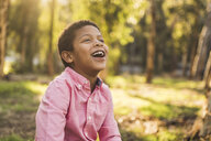 Happy boy looking up while sitting in forest - CAVF50989