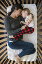 High angle view of mother with son lying in crib at home - CAVF51025