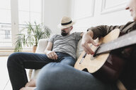Relaxed couple sitting on couch, woman playing the guitar at home - KMKF00607