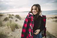 Portrait of smiling woman with cell phone on the beach - RAEF02184