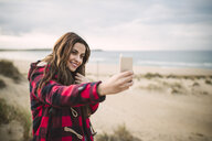 Portrait of smiling young woman taking selfie with smartphone on the beach - RAEF02187