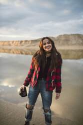 Portrait of laughing young woman with camera standing on the beach - RAEF02190