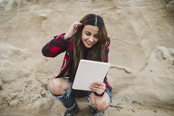 Portrait of smiling young woman using tablet on the beach - RAEF02193