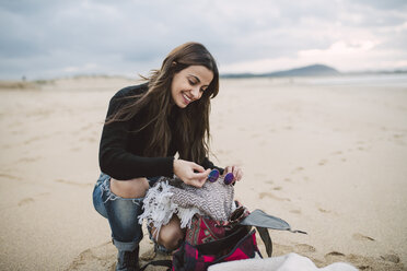 Portrait of smiling woman with backpack on the beach - RAEF02202