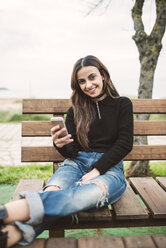 Portrait of smiling young woman with cell phone sitting on bench outdoors - RAEF02208