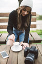 Young photographer sitting on bench outdoors with a cup of coffee - RAEF02214