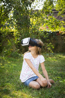 Smiling little girl wearing Virtual Reality Glasses in the garden - LVF07492