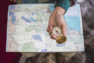 Hand holding compass over map - KKAF02806