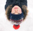 High angle portrait of boy lying on snow covered field - CAVF51057