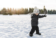Boy playing on snow covered field against sky - CAVF51063